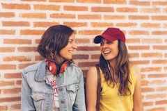 Young women couple looking and smiling each other in a brick wall background. Same sex happiness and joyful scene stock image