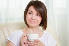 Young women with a cup at home Royalty Free Stock Image