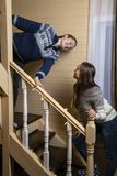 Young women decorate the stairs and laugh. Two young women decorate with garlands a wooden staircase in the house. Preparing for the holiday royalty free stock photos