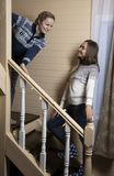 Young women decorate the stairs and laugh. Two young women decorate with garlands a wooden staircase in the house. Preparing for the holiday royalty free stock photo