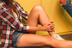 Young women in denim shorts and a bright plaid shirt siting on t Stock Images