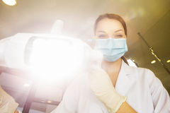Young women dentist with sterile mask readily approaching a patient with dental instruments held in the hands protected with surgi Royalty Free Stock Image