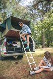 Woman descending ladder form tent over car Royalty Free Stock Photography