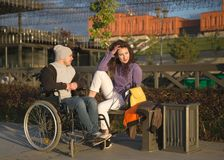 Young woman with disabled man in wheelchair at the quay enjoying sunlight
