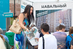 Young women distributes newspapers on campaign for Alexey Navalny Stock Photo