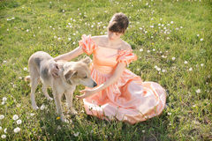 Young Women with dog. Young woman in a pink dress with a dog sitting on the grass Stock Photos