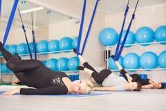 Young women doing aerial yoga exercise or antigravity yoga Stock Photos