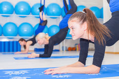 Young women doing aerial yoga exercise or antigravity yoga Stock Photo