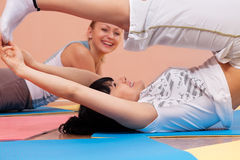 Young women doing bending exercises Stock Photos