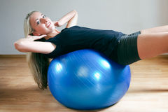 Young women doing crunches on fitness ball. Available light shot Royalty Free Stock Images