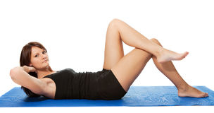 Young women doing crunches on the fitness mat Stock Image