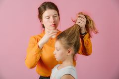 Young woman doing hairstyle girl, in the studio on a pink background stock photos