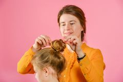 Young woman doing hairstyle girl, in the studio on a pink background stock image