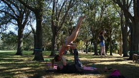 JUPITER, FLORIDA. USA - JUNE 17, 2017. Young women doing acro yoga & slackline on a public park in Florida royalty free stock image