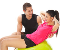 Woman with her personal trainer doing exercises on fitness ball royalty free stock images