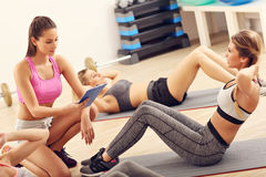 Young women doing sit-ups in a gym Stock Photography