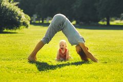 Woman doing yoga with baby in nature stock images