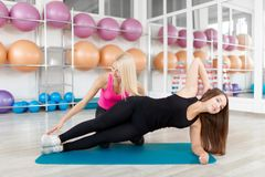 Young woman exercising with her fitness instructor royalty free stock photo