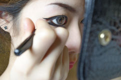 Young women drawing eye liner. She applying eye liner to her eye Royalty Free Stock Photos