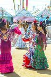 Young women dressed in colourful dresses at the Seville April Fair in Spain.  stock photography