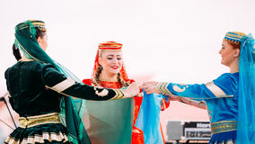 Young women dressed in traditional folk costumes dancing Azerbaijani Stock Photo