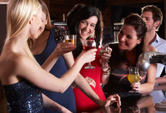 Young women drinking at bar. Smiling royalty free stock images