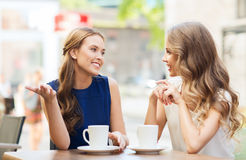 Young women drinking coffee and talking at cafe. People, communication and friendship concept - smiling young women drinking coffee or tea and talking at outdoor Royalty Free Stock Photos