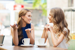 Young women drinking coffee and talking at cafe Stock Image