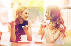 Young women drinking coffee and talking at cafe Stock Images
