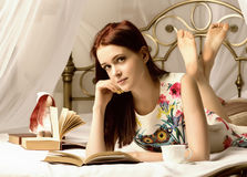 Young women drinking tea and reading a book on a bed at home Stock Photography