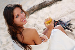 Young women drinking wine on the beach. Young and beautiful women drinking wine on the beach in sunset time royalty free stock image