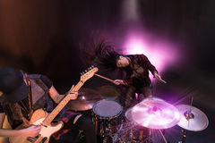 Young women with drums set and electric guitar performing rock concert on stage Stock Photography
