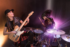 Young women with drums set and electric guitar performing rock concert on stage. Excited young women with drums set and electric guitar performing rock concert stock photos