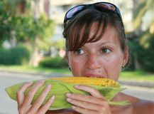 Young women eating messy corn. On the cob Stock Images