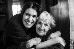 Young woman embracing his elderly mother. Young women embracing his elderly mother. Black and white portrait Royalty Free Stock Photo