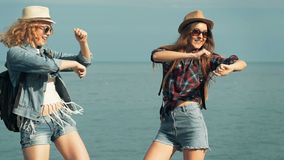Young women enjoying and dancing on a sea shore. stock footage