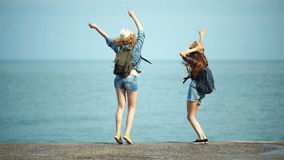 Young women enjoying and dancing on a sea shore.