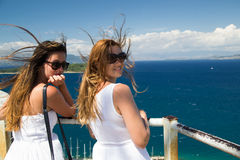 Young women enjoying the landscape. Two young women dressed in white looking at the blue sea on a windy day Stock Image
