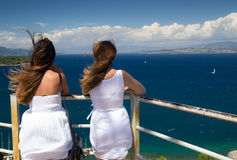 Young women enjoying the landscape. Two young women dressed in white looking at the blue sea on a windy day Stock Images