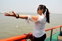 Young women enjoying sea water in mumbai ocean. A young woman standing in a ship and enjoying sea water in mumbai ocean. This is the way of Eliphanta cave stock images