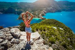 Young women enjoying view to Assos village Kefalonia from top castle. Beautiful blue colored bay lagoon underneath. Young woman enjoying view to Assos village stock images
