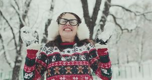 Young women enjoying winter day outdoors. Snow winter landscape snowflakes. SLOW MOTION CLOSE UP: Young smiling woman in winter jacket throwing snowflakes. Happy stock footage