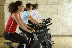 Young women on exercise bikes