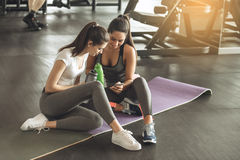 Young women exercise together in the gym. Young female friends exercise in the gym browsing smartphone Stock Photos
