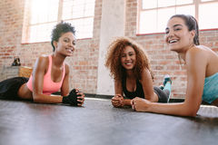 Young women exercising in fitness class. Portrait of three young women in fitness class looking at camera and smiling. Female friends exercising together in Stock Image