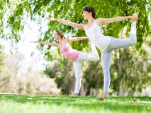 Young women exercising in the park. Healthy and fit young women doing yoga in the park Royalty Free Stock Photos