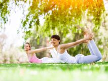 Young women exercising in the park. Healthy and fit young women doing yoga in the park Stock Photography