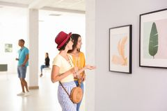 Young women at exhibition. In art gallery stock images