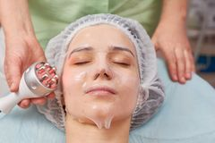 Young woman, facial collagen mask. Young women facial collagen mask. Rf skin tightening device, hand stock photos