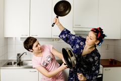 Young Women Fighting In The Kitchen With Pans. Two young women fighting in the kitchen with pans stock photo